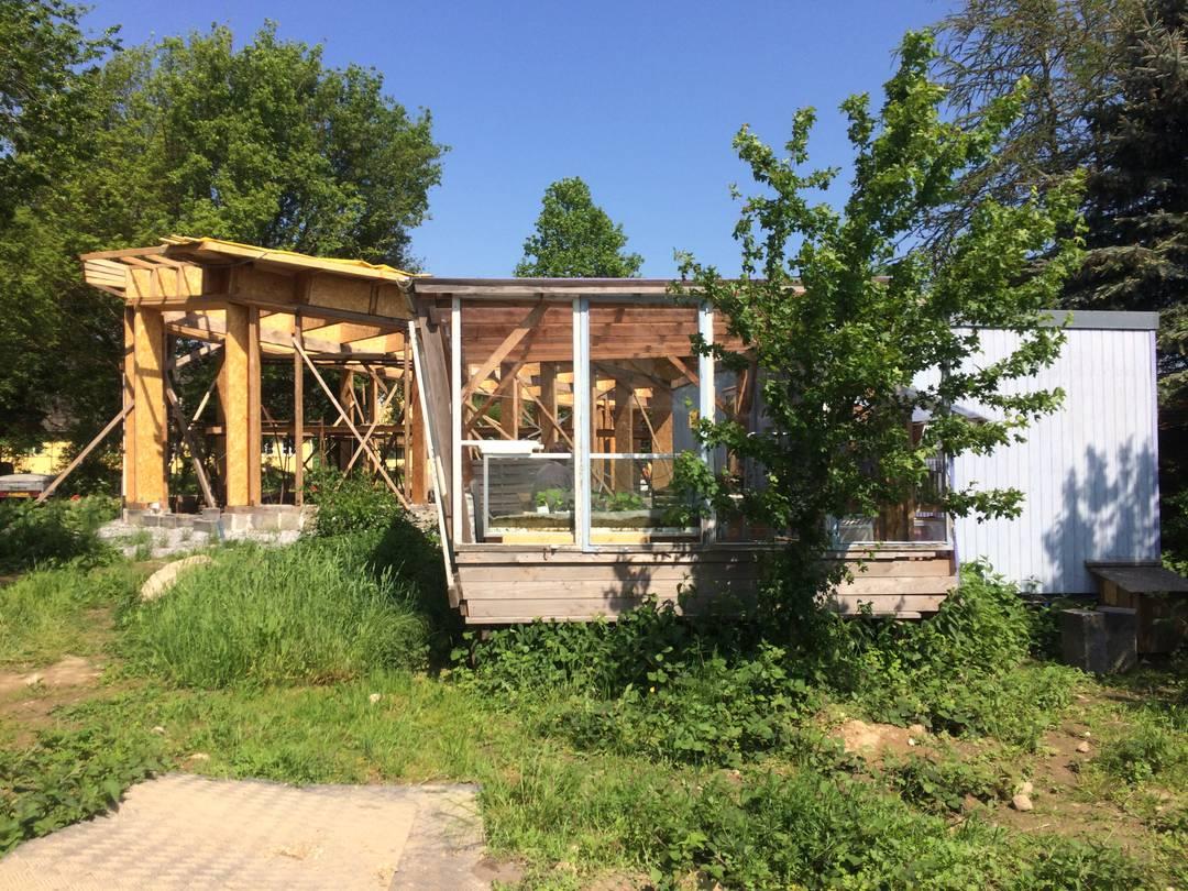 Anna-Marie og Kurt Christensen har i flere år boet her i skurvognen til højre. Men nu er de ved at bygge deres nye halmhus (i baggrunden til venstre). Foto: Palle Søby